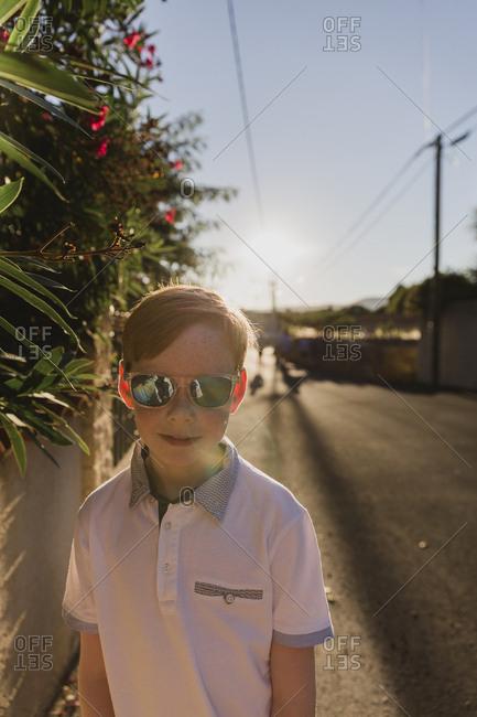 Portrait of boy wearing mirrored sunglasses at evening twilight