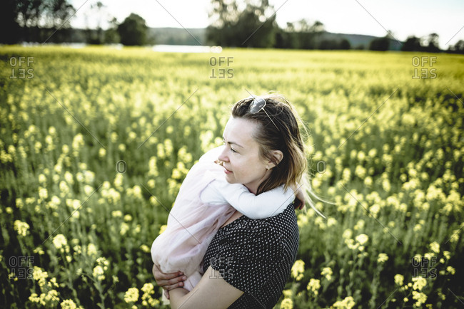 Little girl on her mother's arms in rape field