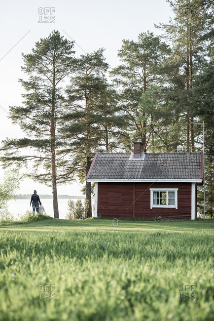 Finland- Kuopio- mother with daughter at a cottage by the lakeside in the countryside