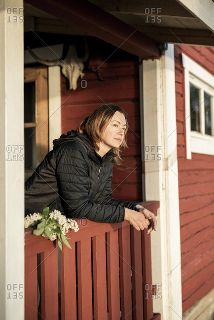 Finland- Kuopio- woman on the veranda of a cottage in the countryside