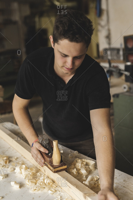 Carpenter using plane on piece of wood in workshop