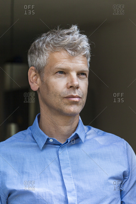 Portrait of pensive mature man with grey hair wearing blue skirt