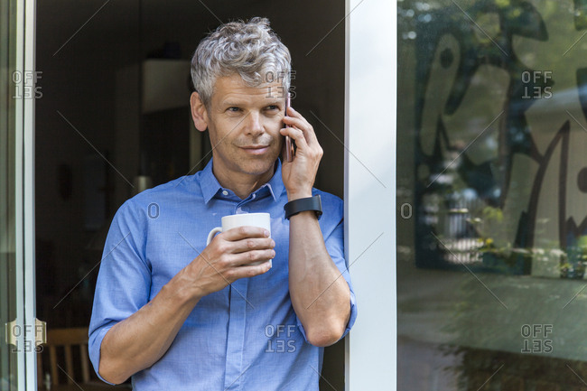 Portrait of mature man on the phone leaning against door case with coffee mug