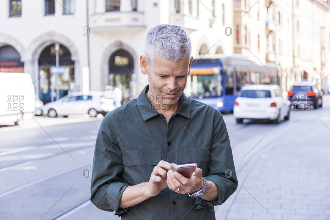 Mature man using cell phone in the city
