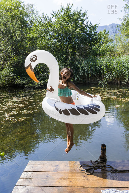 Carefree girl jumping into pond with inflatable pool toy in swan shape