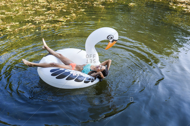 Girl floating in water on inflatable pool toy in swan shape
