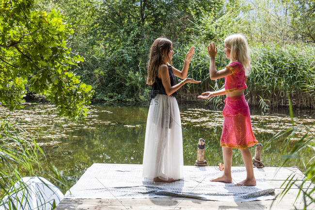 Two girls standing on jetty at a pond in fancy dresses doing a hand clapping game