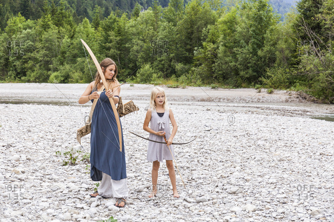Mother and daughter with bow and arrow in the nature