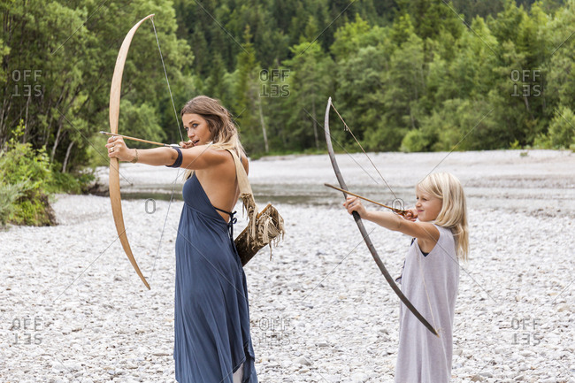 Mother and daughter aiming with bow and arrow in the nature