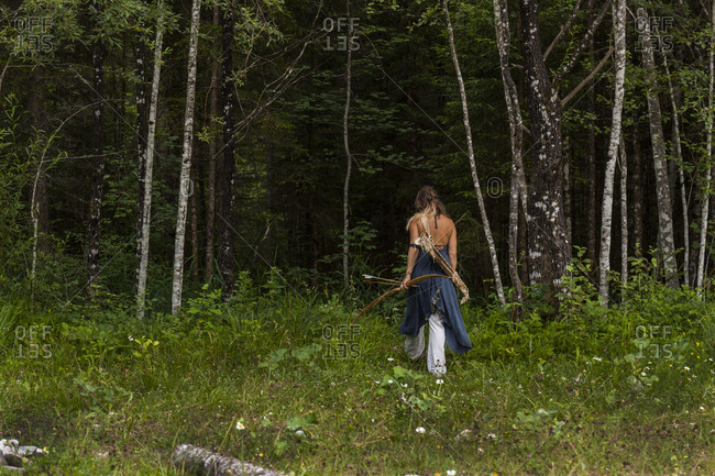 Rear view of woman walking in a forest with bow and arrow