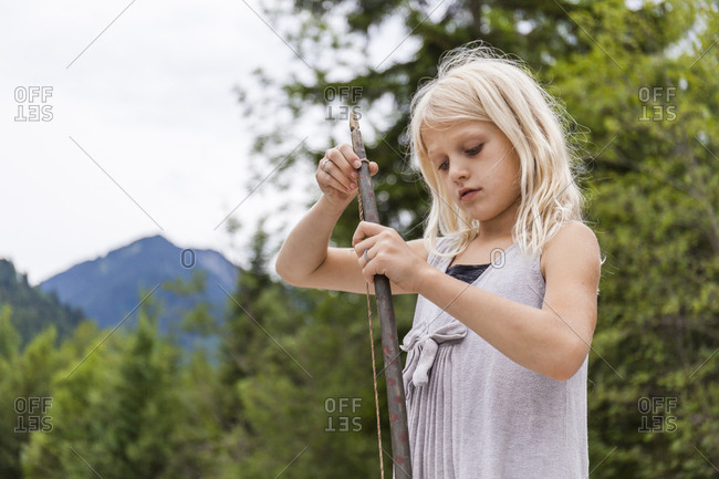 Girl holding a self-made bow outdoors
