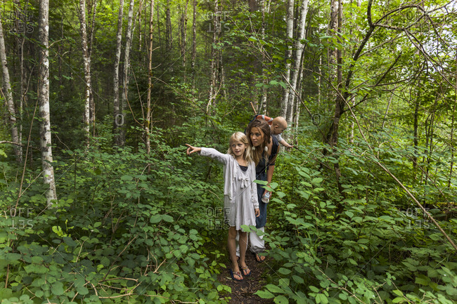 Girl hiking in the woods showing the way to mother and little brother