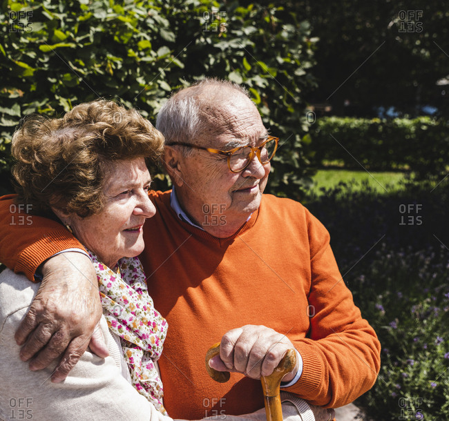 Senior couple sitting on bench in a park- with arms around