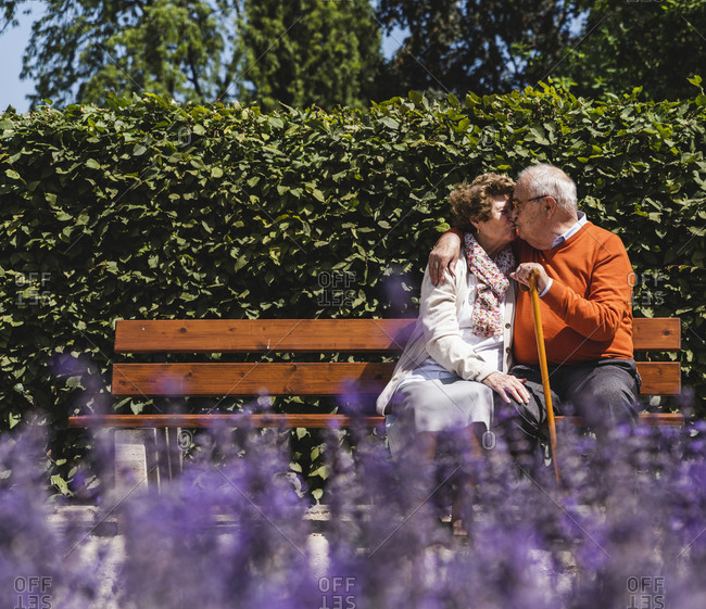 Senior couple sitting on bench in a park- kissing