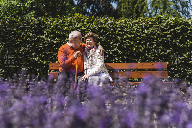 Senior couple sitting on bench in a park- falling in love