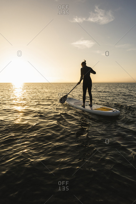 Young woman stand up paddle surfing at sunset