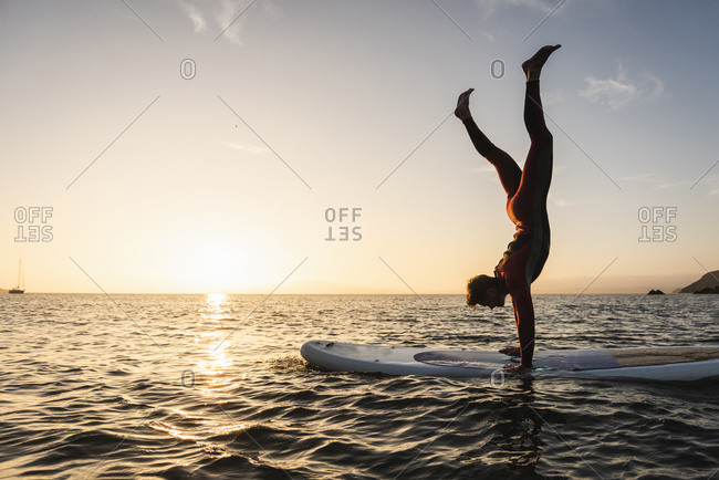 Young man doing handstand on paddleboard at sunset