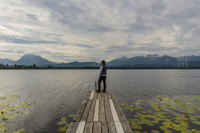 Germany- Bavaria- Allgaeu- Lake Hopfensee- woman standing on jetty