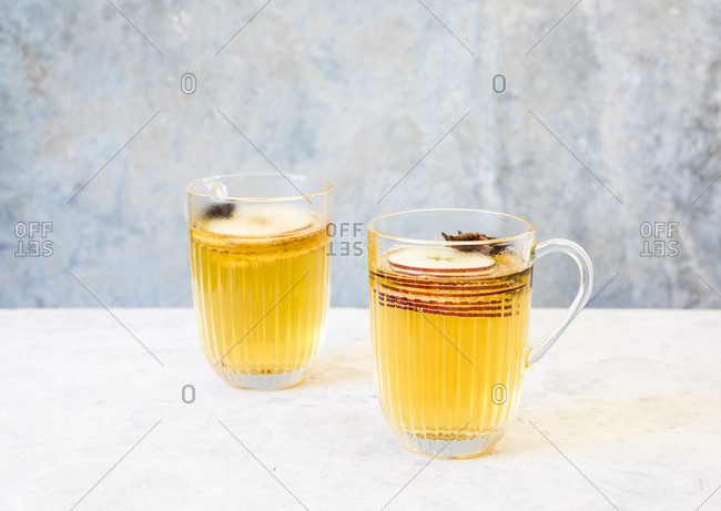 Apple cider served with slices of fresh apples