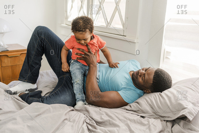 Mid adult father playing with son while lying in bed at home