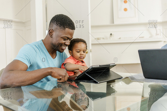 Smiling father with son using digital tablet at table