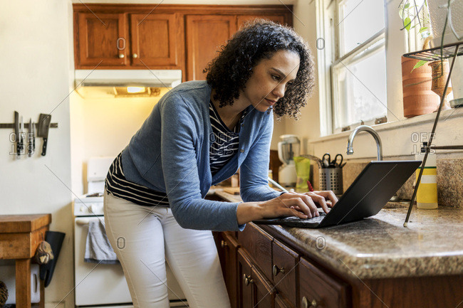 Confident mid adult woman using laptop at kitchen counter