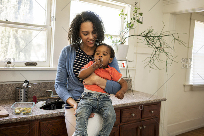 Smiling mother carrying son having food in kitchen at home