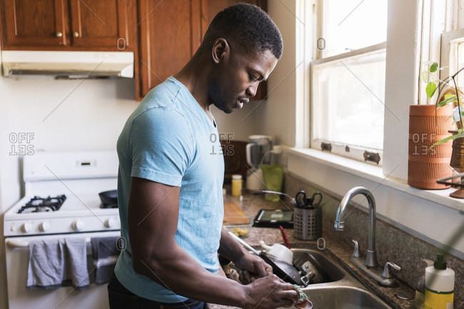 Side view of mid adult man washing utensil at kitchen sink