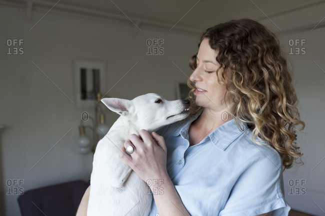 Beautiful mid adult woman petting dog while standing at home