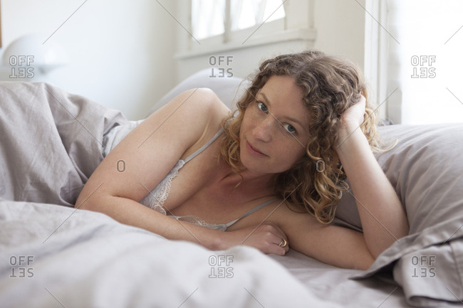 Portrait of sensuous mid adult woman lying on bed at home