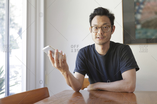 Portrait of confident mature man holding smartphone while sitting at table in home