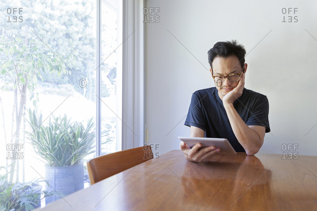 Mature man using digital tablet while sitting at dining table by window at home