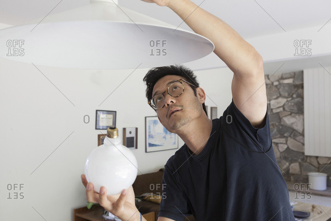 Mature man changing lightbulb in living room at home