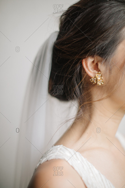 Close up of a bride wearing gold and diamond earrings