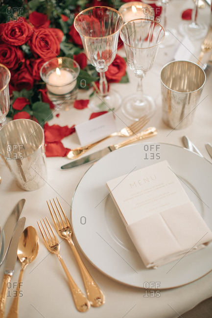 Place setting at a wedding with red roses and candles