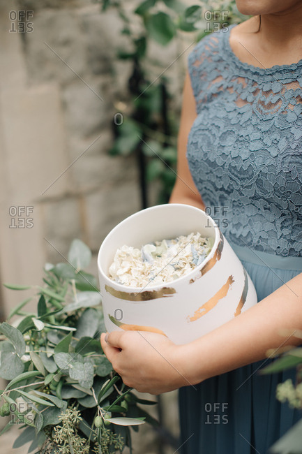 Bridesmaid holding a container of flower petals