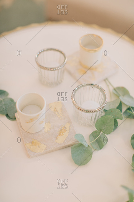 Place setting at a wedding with candles and eucalyptus leaves