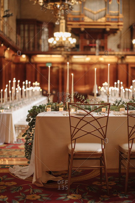 Tables with lit candles and eucalyptus leaves at a wedding reception