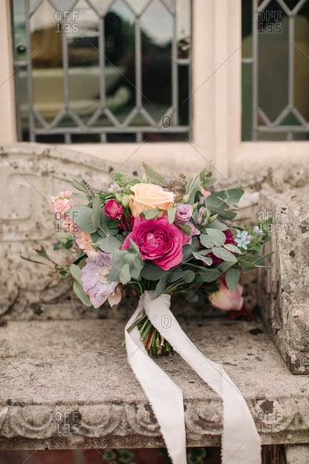 Colorful wedding bouquet on a stone bench
