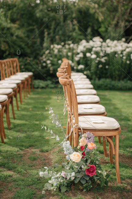Flowers on the end of a row of chairs at a wedding ceremony