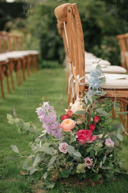 Flower arrangement on the end of a row of chairs at a wedding ceremony