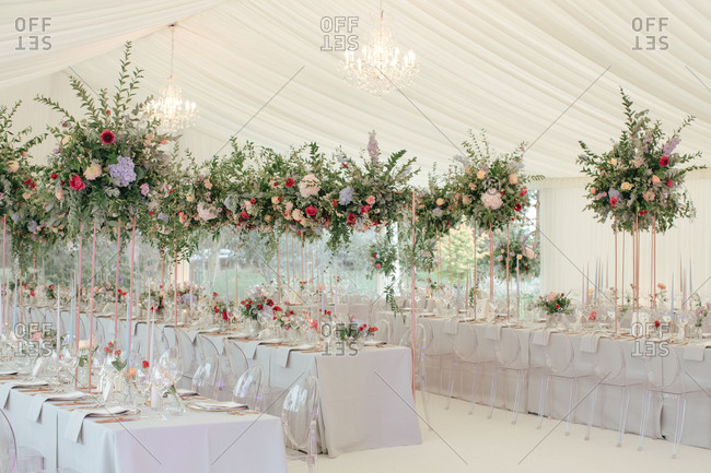 Tables with large flower arrangement at a wedding reception in a tent