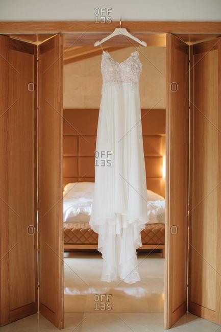 Beautiful wedding dress hanging from door frame