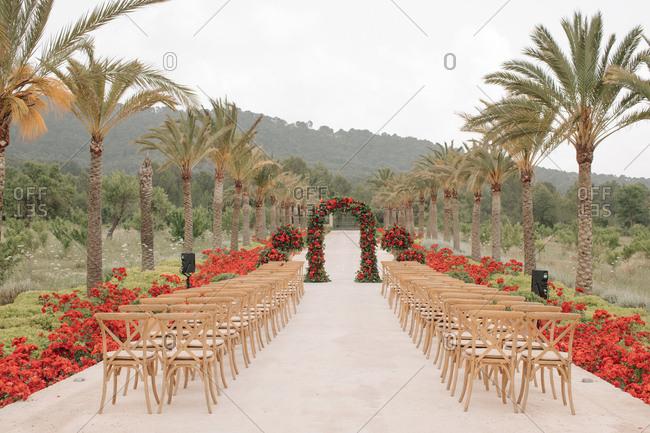 Beautiful outdoor wedding ceremony with red flowers and palm trees