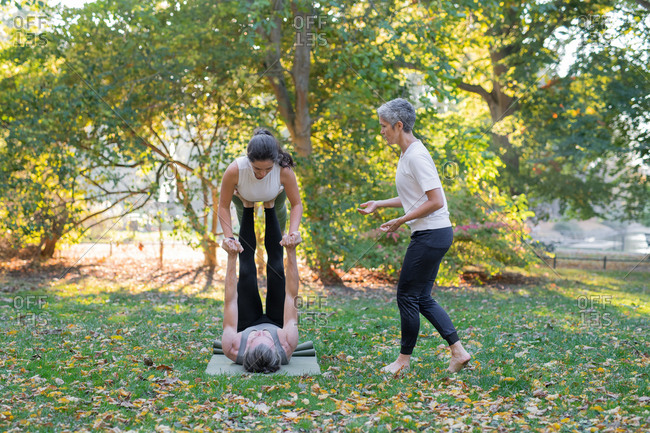 Three people doing yoga in park