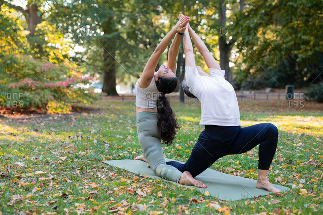 Two women doing yoga pose in park