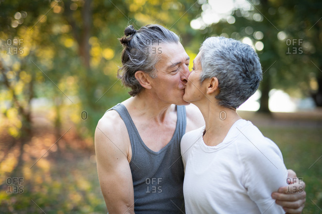 Senior couple kissing during yoga workout in park