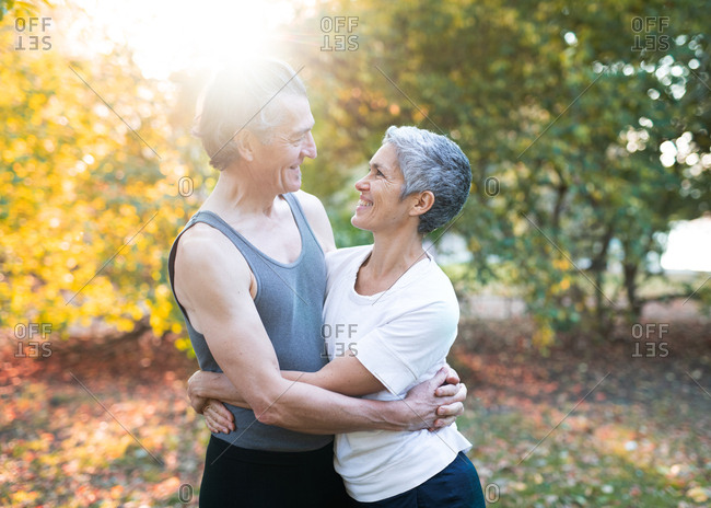 Senior couple embraced during yoga workout in park