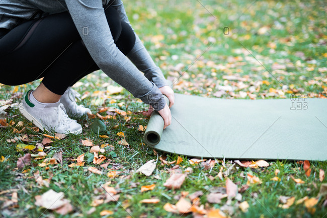 Woman rolling up yoga mat in park