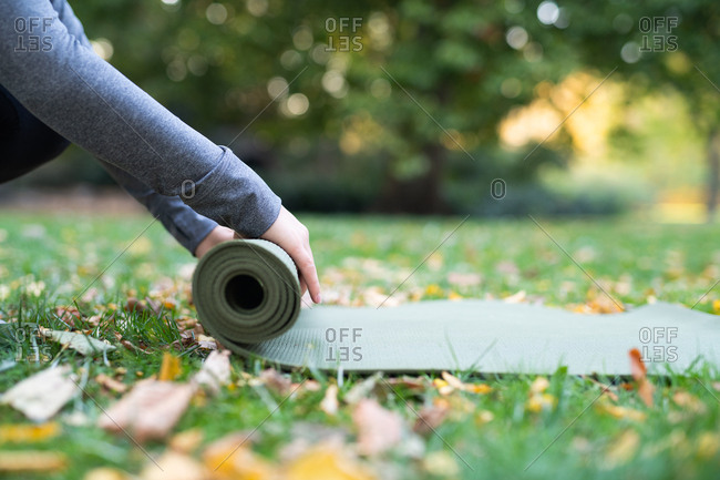 Close up of woman rolling up yoga mat in park